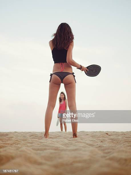Two girls playing beach paddle ball