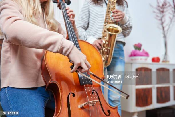 Two girls playing cello and saxophone together