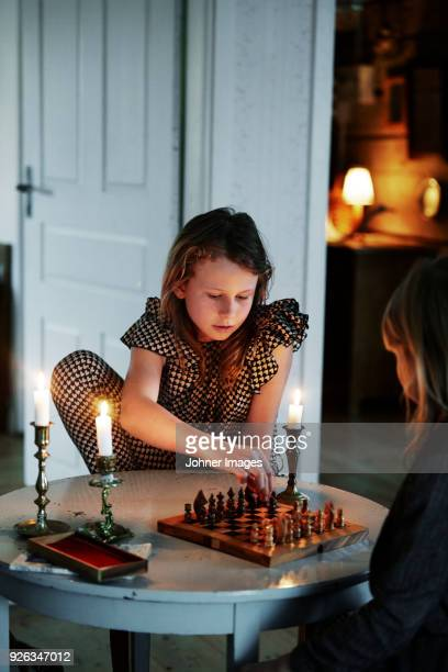 Two girls playing chess in living room