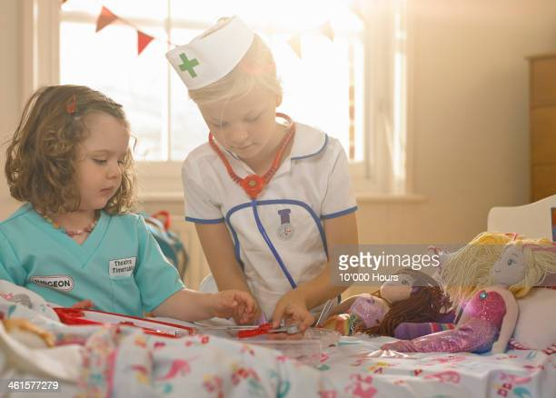 two girls playing, dressed as doctor and nurse - doll stock pictures, royalty-free photos & images