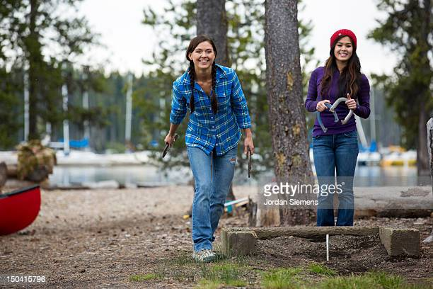 two girls playing horseshoes. - horseshoe stock pictures, royalty-free photos & images