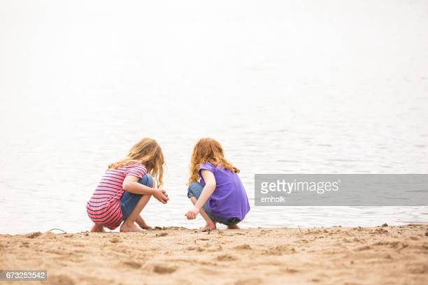 two girls playing in sand at beach in early springtime - lake auburn stock photos and pictures
