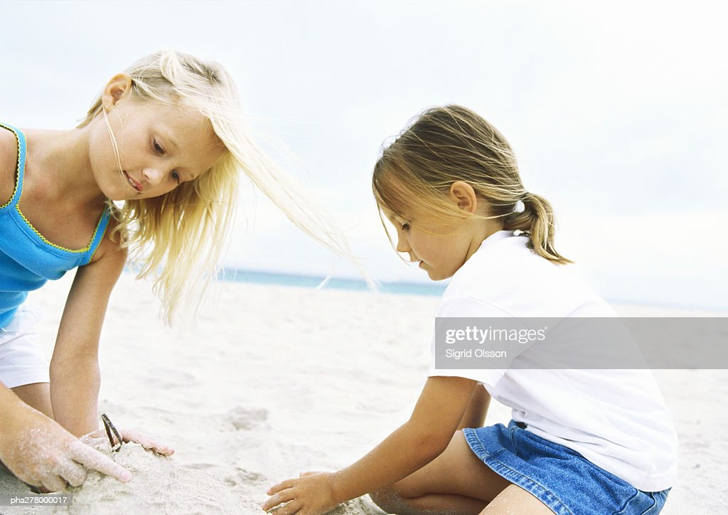 Two girls playing in sand : Stockfoto