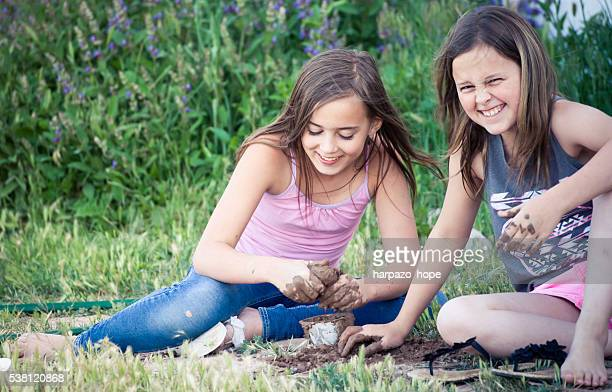 Two girls playing in the mud.
