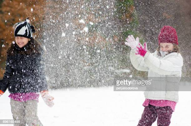 Two girls playing in the snow