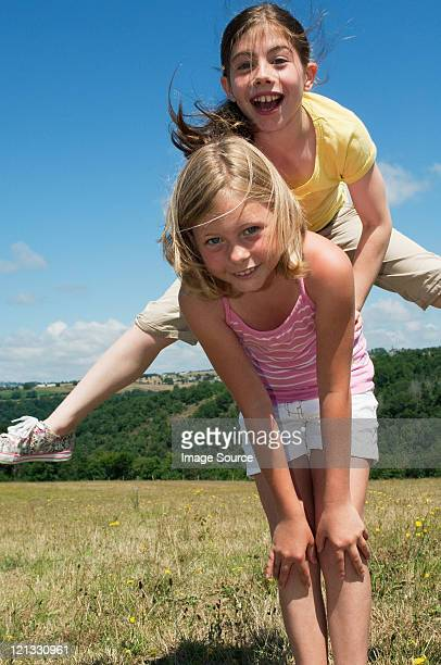 Two girls playing leapfrog in field