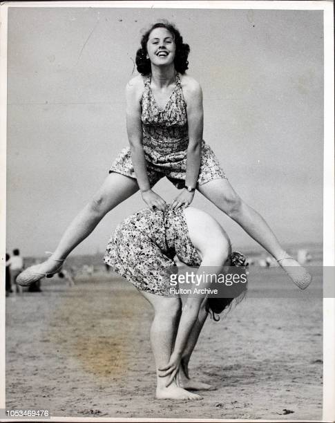 Two girls playing leapfrog on the beach at Bridlington, UK, circa 1935.