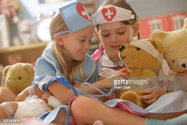 two girls playing nurse with toys - medical symbol stock pictures, royalty-free photos & images
