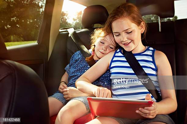 Two girls playing on digital tablet