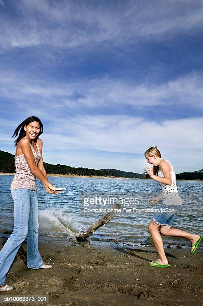 two girls (11-14 years) playing on edge of lake - 14 15 years stock pictures, royalty-free photos & images