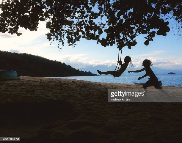 two girls playing on swings on the beach, rio de janeiro, brazil - taken on mobile device stock photos and pictures