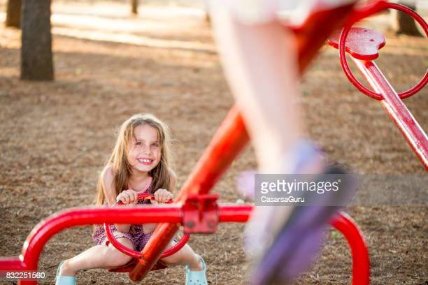 Two Girls Playing On The Seesaw In The Public Park