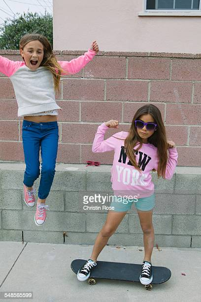 Two girls playing, one on skateboard