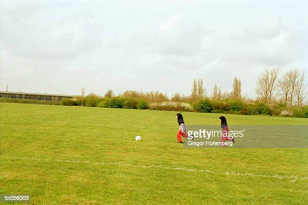 Two girls playing soccer