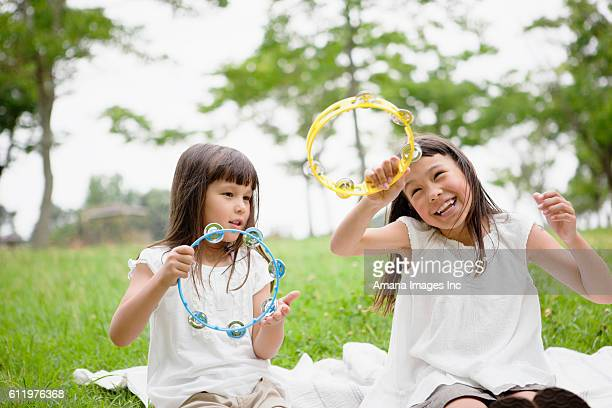 two girls playing tambourines - tambourine stock pictures, royalty-free photos & images