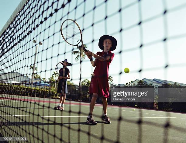 two girls (7-11) playing tennis - blasius erlinger stock pictures, royalty-free photos & images