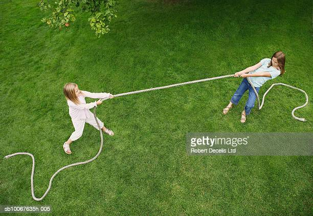 Two girls (6-9 years) playing tug of war on lawn, elevated view