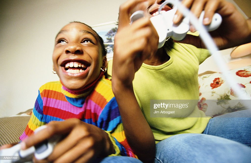Two girls (8-15) playing video games : Stock Photo