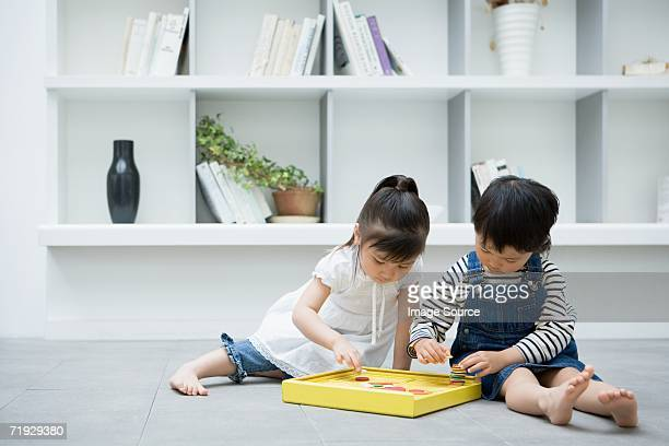 two girls playing with a toy - a sense of home stock photos and pictures