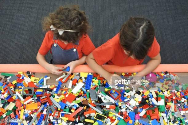 two girls playing with building bricks - rafael ben ari fotografías e imágenes de stock