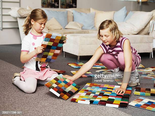 Two girls (7-10) playing with carpet samples on floor