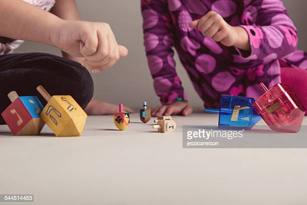 two girls playing with dreidels to celebrate hanukkah - hanukkah imagens e fotografias de stock