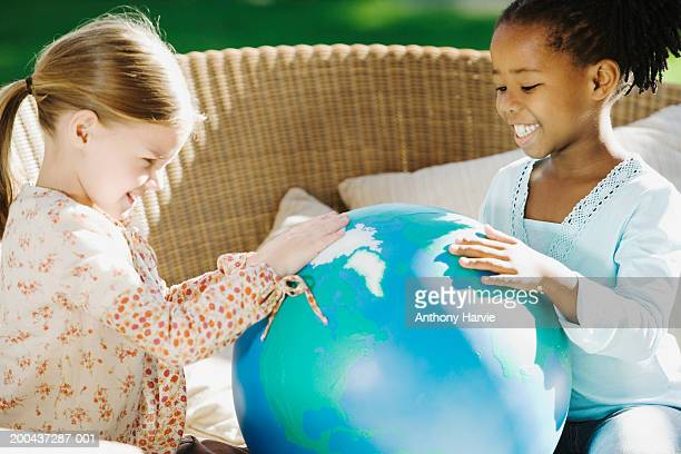 Two girls (4-6) playing with globe in garden, smiling