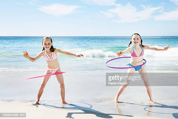 two girls (6-11) playing with hula hoops on beach, smiling - girl with legs spread stock photos and pictures