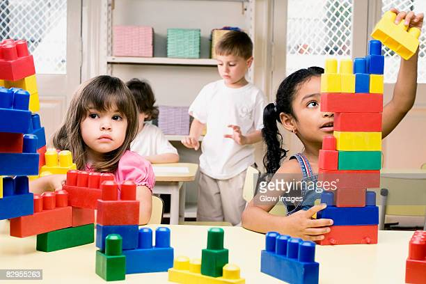 Two girls playing with plastic blocks with their friends in the background