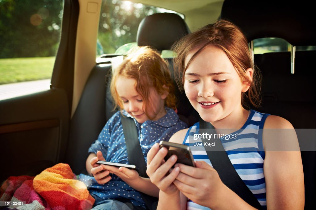 Two girls playing with smart phone in car : Stockfoto