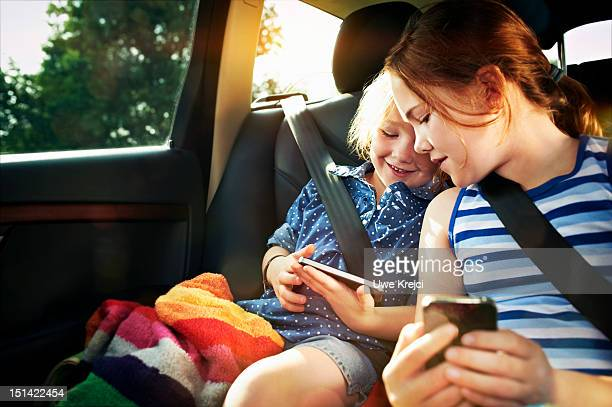 Two girls playing with smart phone in car