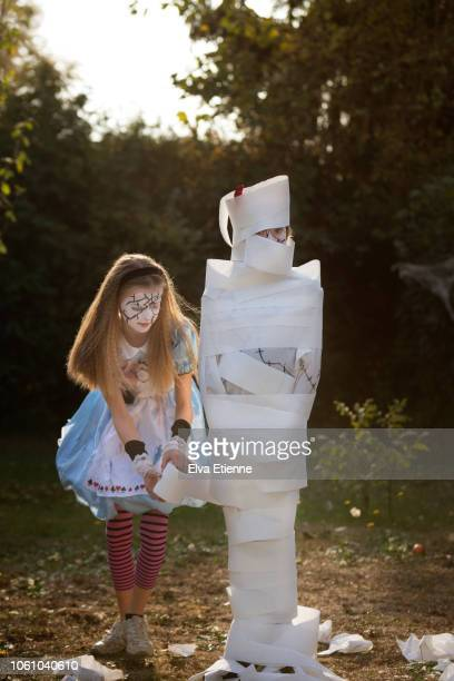 two girls playing 'wrap the mummy' halloween game with toilet roll - wrapped in toilet paper stock pictures, royalty-free photos & images