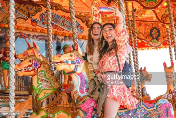 Two girls pose for a selfie while riding on the carousel on Brighton beach as thousands flock to the seaside to make the best of the Bank Holiday...