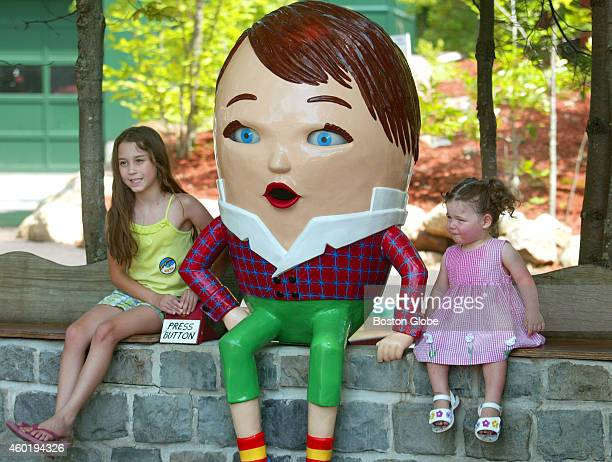 Two girls pose for pic at the Humpty Dumpty sculpture just inside the gates of Story Land just as their parents had done years ago