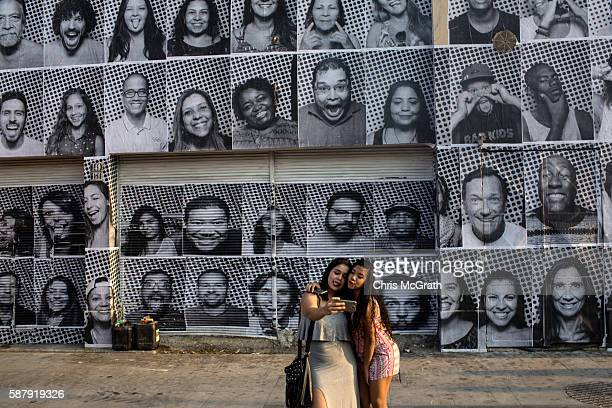 Two girls pose in front of portraits produced by artist JR for his inside out project on August 8 2016 in Rio de Janeiro Brazil The artist JR has...