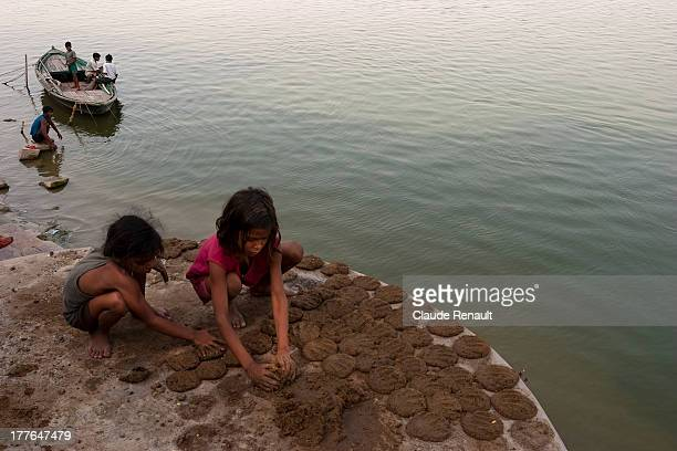 Two girls preparing cakes of cow dung to dry by the Ganges. A cheap fuel..