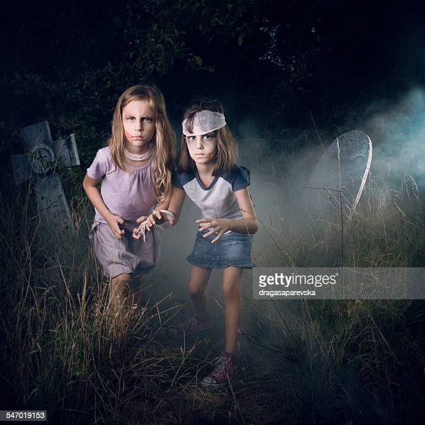 Two girls pretending to be zombies in a cemetery at Halloween