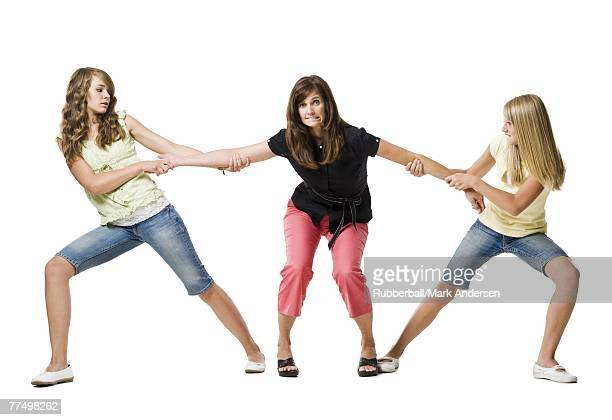Two girls pulling mother's arms in both directions