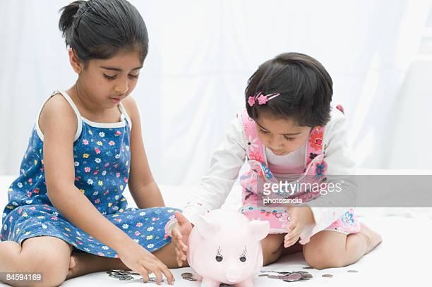 Two girls putting coins in a piggy bank