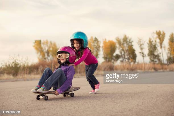 two girls racing on a skateboard - pushing stock pictures, royalty-free photos & images