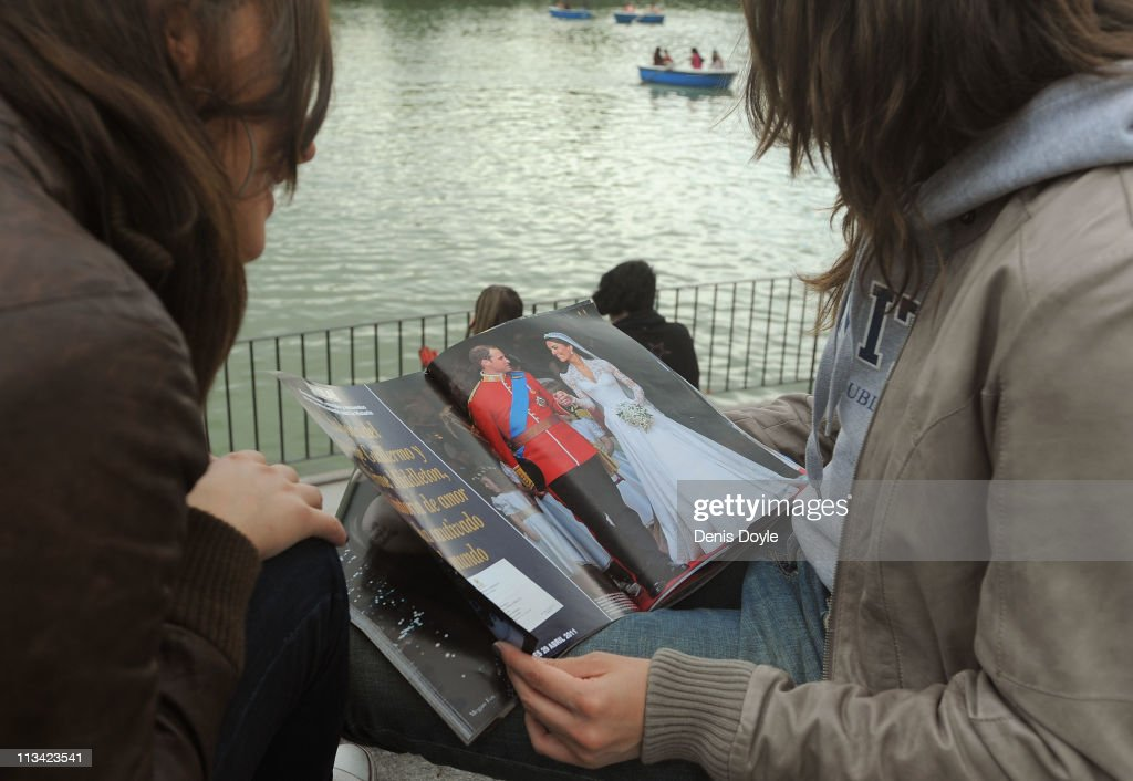 Two girls read a Spanish magazine at Retiro park showing photographs of their Royal Highnesses Prince William, Duke of Cambridge and Catherine, Duchess of Cambridge following their wedding, on May 2, 2011 in Madrid, Spain. The marriage of the second in line to the British throne was led by the Archbishop of Canterbury and was attended by 1900 guests, including foreign Royal family members and heads of state. Thousands of well-wishers from around the world flocked to London to witness the spectacle and pageantry of the Royal Wedding.