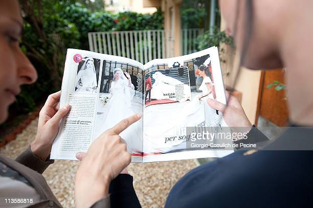 Two girls read an Italian magazine showing photographs of Prince William Duke of Cambridge and Catherine Duchess of Cambridge following their wedding...