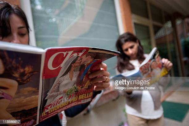 Two girls read Italian magazines showing photographs of Prince William Duke of Cambridge and Catherine Duchess of Cambridge following their wedding...