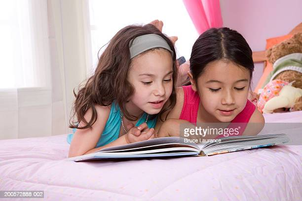 Two girls (6-7) reading book on bed