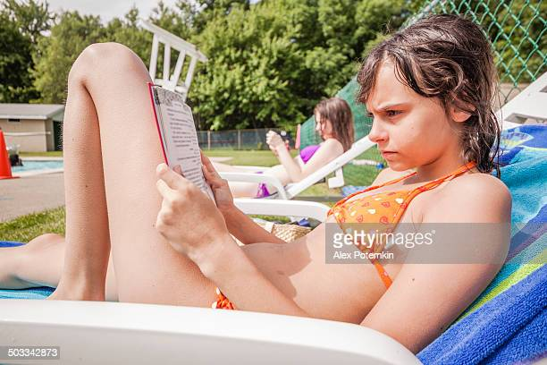two girls reading books next to the public pool - girls sunbathing stock photos and pictures