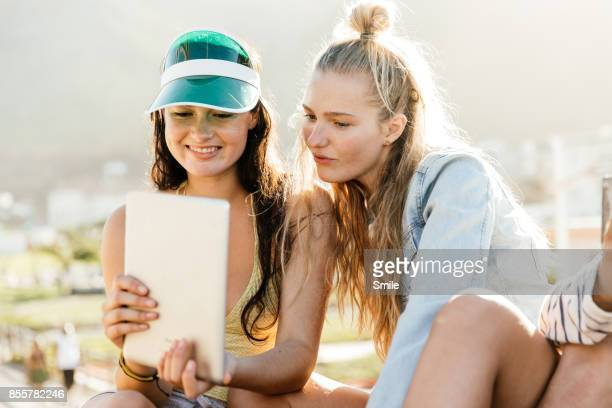 Two girls reading from tablet