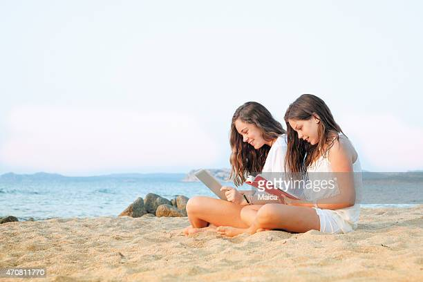 Two girls reading in a beach