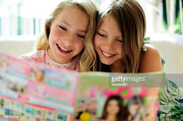 two girls reading teen magazine - somente crianças imagens e fotografias de stock