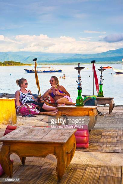 Two girls relaxing by water near hookah pipes.