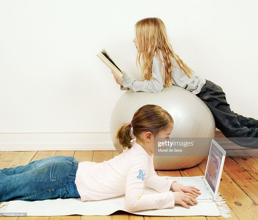 Two Girls Relaxing In Living Room Reading And Looking At Laptop High Res Stock Photo Getty Images